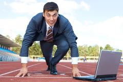 Image of businessman getting ready for race with laptop near by Stock Photos