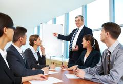 Smart and confident boss pointing at whiteboard and looking at managers during p Stock Photos