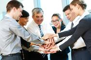 Stock Photo of photo of smiling co-workers making pile of hands and looking at camera