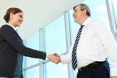 photo of successful partners handshaking after striking deal - stock photo