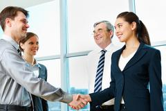 Stock Photo of photo of successful partners handshaking after signing agreement at meeting