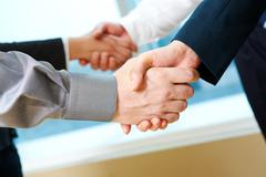 photo of two pairs of partners arms handshaking after striking deal - stock photo