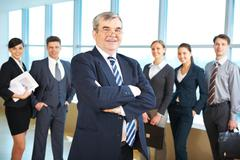 Image of senior leader smiling at camera with several employees behind Stock Photos