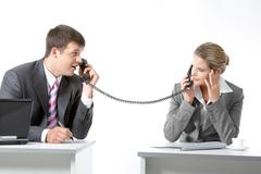Portrait of business partners speaking on the telephone and looking at each othe Stock Photos