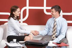 Portrait of business partners handshaking at meeting and looking at each other Stock Photos