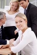 portrait of a young woman against her colleagues - stock photo