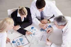 Stock Photo of above view of business team working with graphics