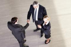 Senior manager shaking hands with his partner, their colleague clapping Stock Photos