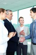 Photo of successful businessmen handshaking after striking deal with applauding Stock Photos