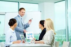 A business man showing something on a whiteboard to his colleagues Stock Photos