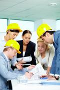 Stock Photo of group of architects looking at a project and discussing it