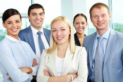 portrait of friendly leader looking at camera with several employees behind - stock photo