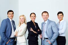 A business team of five looking at camera and smiling Stock Photos
