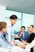 group of business people discussing papers or sharing ideas in office - stock photo