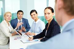 Group of business people looking at their employer while consulting in office Stock Photos