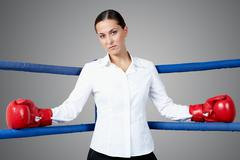 portrait of strict businesswoman in boxing gloves looking at camera - stock photo