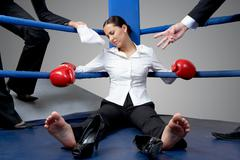 portrait of tired businesswoman in boxing gloves sleeping on boxing ring after h - stock photo