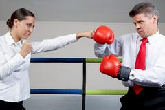 portrait of aggressive businessman in boxing gloves fighting with serious female - stock photo