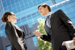 Photo of confident businessman looking at associate while communicating with her Stock Photos