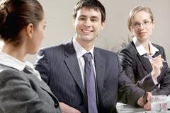 Portrait of happy businessman looking at colleague with another woman near by Stock Photos