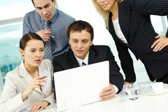 portrait of several colleagues looking at laptop screen in office - stock photo