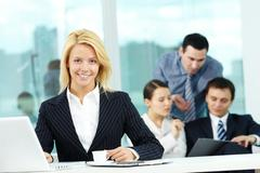 portrait of pretty secretary looking at camera in working environment - stock photo