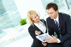 Portrait of confident man and woman discussing document in office Stock Photos