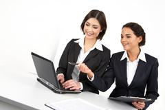 two businesswomen working together with computer - stock photo
