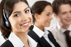 close-up of a young businesswoman in headset looking at camera and smiling - stock photo