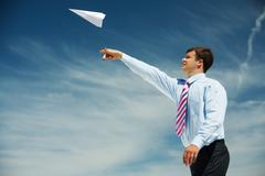 Image of businessman letting paper airplane fly and looking at it on background Stock Photos