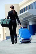 rear view of businesswoman in suit walking with her baggage and bag - stock photo