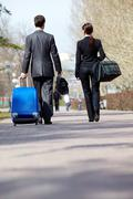 Stock Photo of rear view of business partners in suits walking with baggage