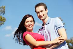 Portrait of happy couple looking at camera against blue sky Stock Photos