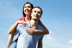 happy man giving piggyback to his wife outdoors against blue sky - stock photo