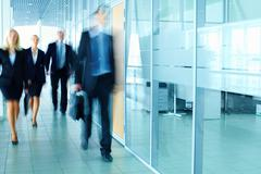 blurred figures of business people walking along the corridor - stock photo
