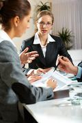image of young female listening to explanation of business partner at meeting - stock photo