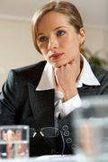 Image of young female looking aside while listening to somebody at meeting Stock Photos