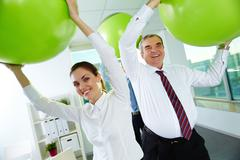 Portrait of joyful business partners playing with big balls in office Stock Photos