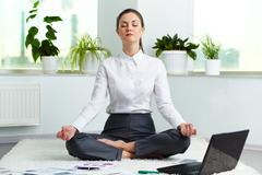 portrait of attractive white collar worker meditating in office - stock photo