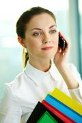 a beautiful businesswoman talking by cellular phone in office - stock photo