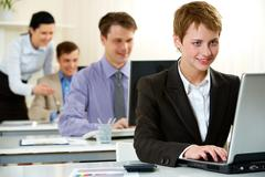 Young woman working on computer in office with other people Stock Photos