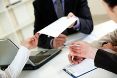 Businessman giving document to his colleagues Stock Photos