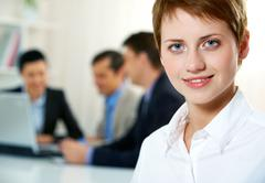 Close-up of young office worker with her colleagues in the background Stock Photos