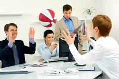 Businesspeople throwing basketball in the office Stock Photos