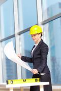 a young woman architect in helmet examining a plan - stock photo