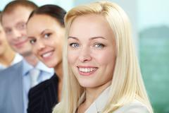 Businesspeople standing in a row, the focus is on blond woman Stock Photos