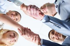 Below view of four people handshaking Stock Photos
