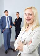 Stock Photo of portrait of young businesswoman with two colleagues in the background
