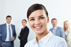 young businesswoman looking at camera and smiling against her colleagues - stock photo