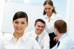 Young woman looking at camera and smiling against her communicating colleagues Stock Photos